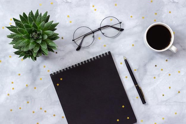 オフィスや自宅のテーブルデスク。黒のメモ帳、ペン、一杯のコーヒー、大理石の背景に多肉植物