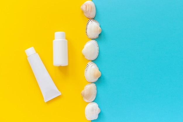 白いチューブ、黄色と青の背景、モックアップに日焼け止めとラインの貝殻のボトル