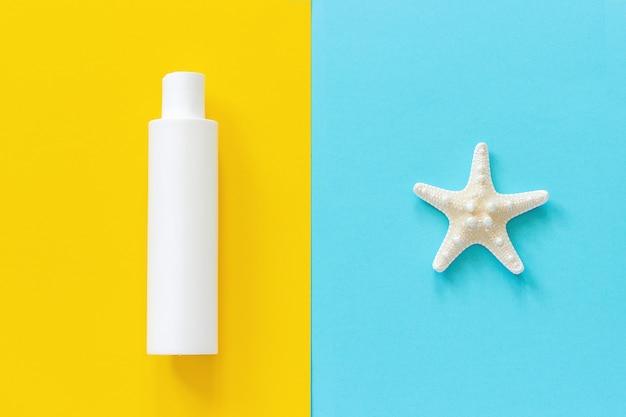 海のヒトデと黄色と青の紙の背景に日焼け止めの白いボトル。モックアップ