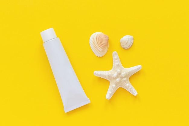 海のヒトデ、貝殻、黄色い紙の背景に日焼け止めの白い管。モックアップ