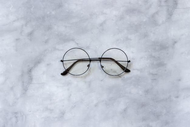 Стильные черные круглые очки очки на фоне мрамора.