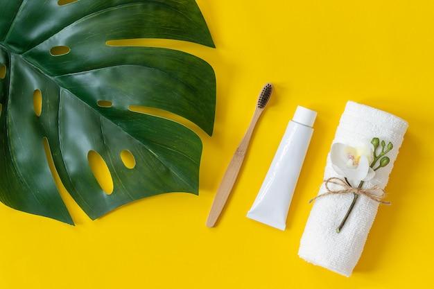 天然の環境に優しい竹のブラシ、タオル、練り歯磨きのチューブ、熱帯の葉のモンステラ。