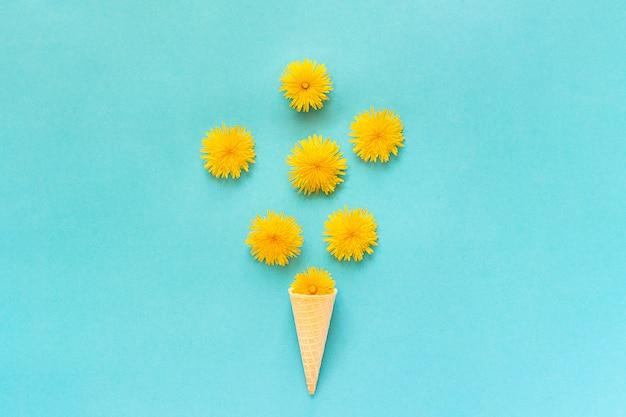 青い背景にワッフルアイスクリームコーンの花束タンポポの花
