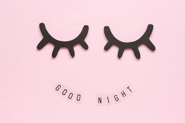 テキストおやすみと装飾的な木製の黒いまつげ、ピンクの背景に目を閉じて