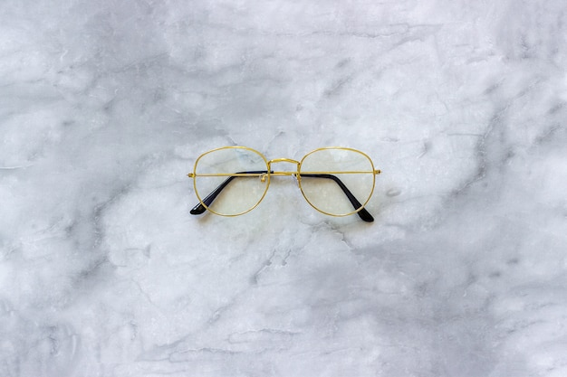 大理石の背景にスタイリッシュなゴールド眼鏡メガネ。最小限のスタイル