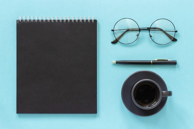 オフィスや自宅の職場。黒い色のメモ帳、一杯のコーヒー、眼鏡、青の背景にペン