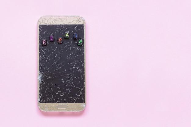 ピンクの壊れたひび割れ携帯電話とテキストの修復