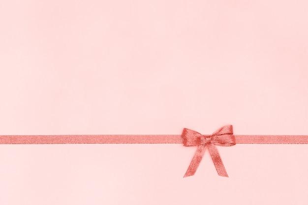Декоративная блестящая лента с бантом на пастельно-розовом