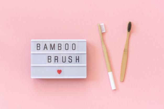 Две натуральные экологически чистые бамбуковые щетки и текст лайтбокса бамбуковая кисть на розовом