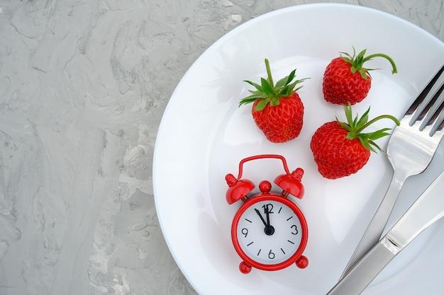 Красные спелые ягоды клубники на белом фоне, столовые приборы и красный будильник на сером каменном столе, крупным планом