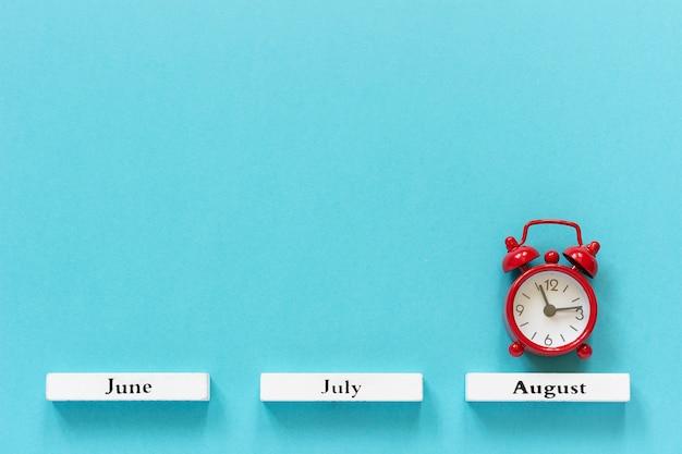 Календарь летних месяцев и красный будильник за август на синем. концепция августовского времени