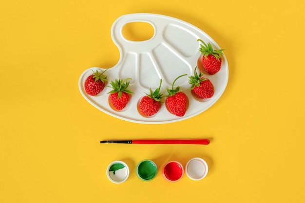 芸術的なパレット、ブラシ、黄色のガッシュに赤の熟したイチゴ