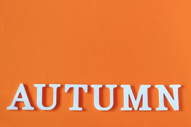 オレンジ色の紙の背景、最小限のスタイルにコピースペースを持つ白い文字から単語秋