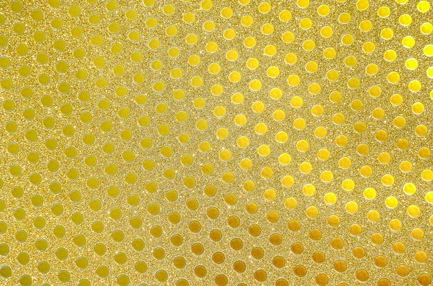 黄金の包装紙、背景またはテクスチャとしてちらつきの小さな円