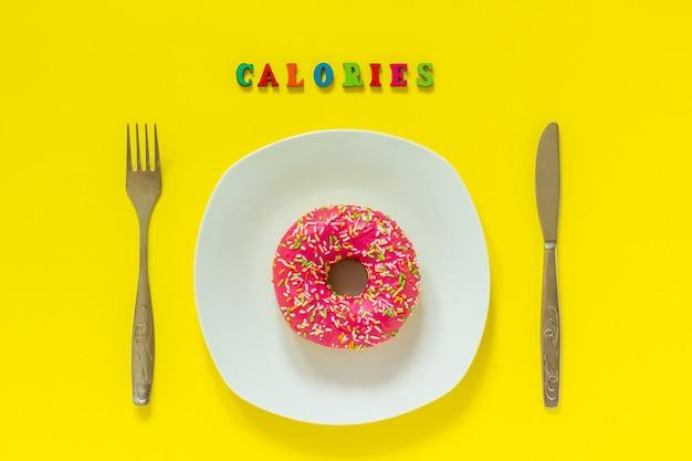 カロリーと白い皿の上のピンクのドーナツと黄色の背景にナイフフォーク。