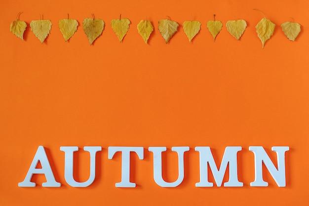 秋の組成物。白い文字と明るい秋から単語秋はオレンジ色の背景に標本を残します。