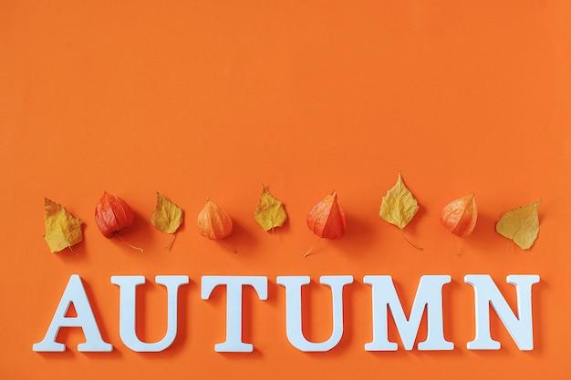秋の組成物。白い文字と明るい秋から単語秋はオレンジ色の紙の背景に標本を残します