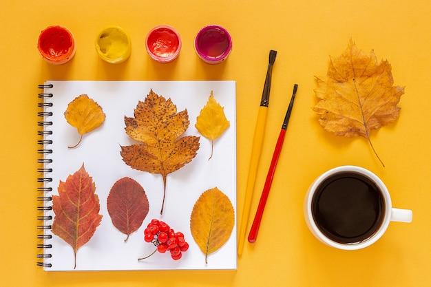 明るい秋の組成。スクラップブックと水彩絵の具、絵筆に着色された葉標本。上面図