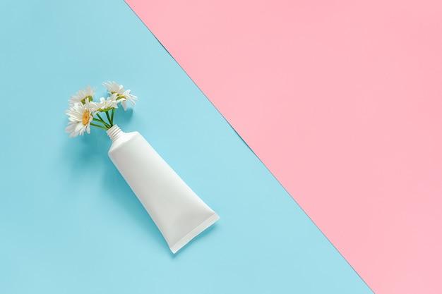化粧品、クリーム、軟膏、歯磨き粉または他の製品の医療用白いチューブからのカモミールの花の花束