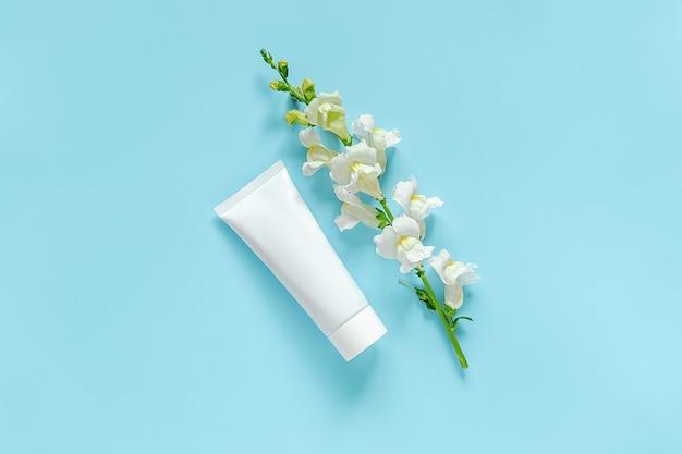 白い花と化粧品、クリーム、軟膏、歯磨き粉用の医療用白いチューブ。天然オーガニック化粧品
