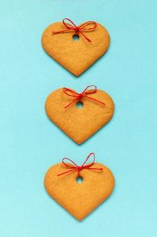 青の背景に弓で飾られたハート型のジンジャークッキー