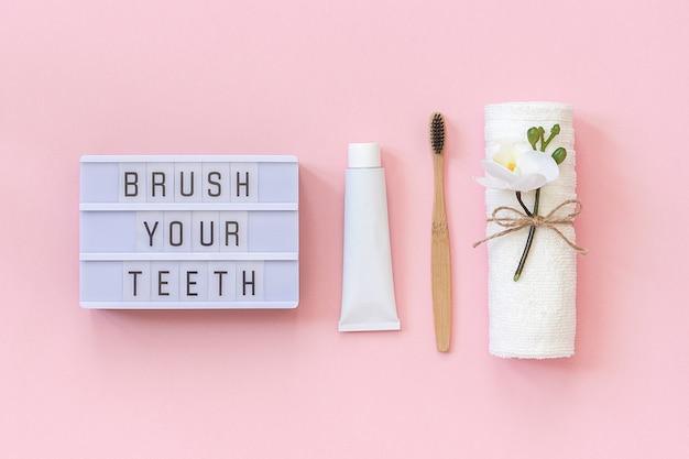 歯を磨く-歯、タオル、歯磨き粉チューブ用のライトボックステキストと自然に優しい竹ブラシ。