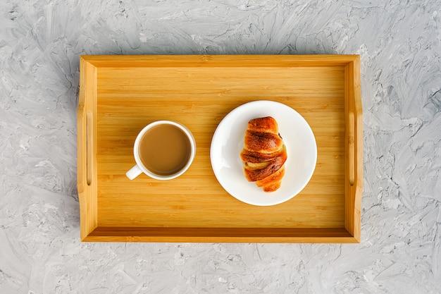 Чашка кофе с молоком и свежеиспеченный круассан на деревянный поднос на сером каменном столе