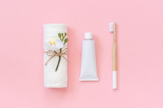 自然な環境に優しい竹のブラシ、白いタオル、歯磨き粉のチューブ。