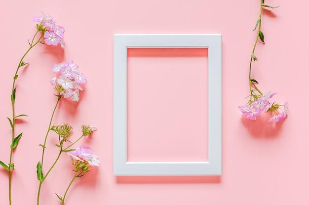 白い木製の写真フレームとコピースペースとピンクの背景の花。