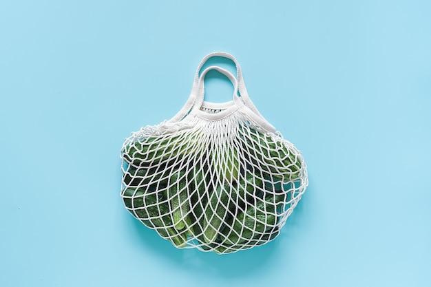 Овощи свежие зеленые огурцы в многоразовых покупок эко дружественных сетки мешок на синем фоне.
