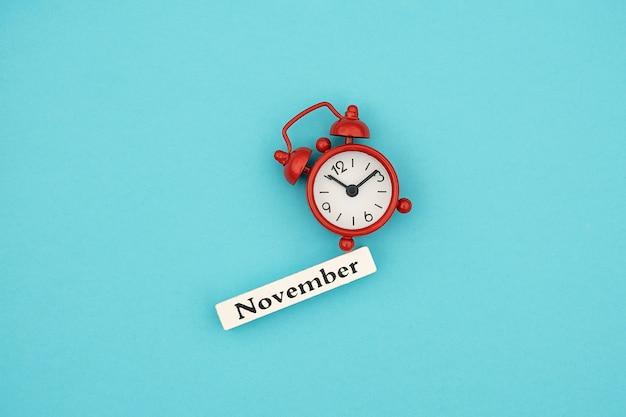 Деревянный календарь осенний месяц ноябрь и красный будильник на синем фоне бумаги. привет, сентябрь