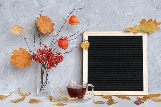 空白の黒い文字ボードフレームと花瓶の洗濯はさみに黄色の葉と枝の秋の花束