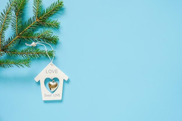 青の背景にモミの枝に白いクリスマス装飾おもちゃの家。コンセプトメリークリスマスまたは新年あけましておめでとうございます。