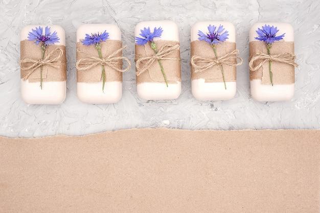 クラフト紙、スカージ、青い花で飾られた手作りの天然石鹸セット。オーガニック化粧品のコンセプト。