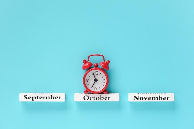 Деревянный календарь осенних месяцев и красный будильник на октябрь