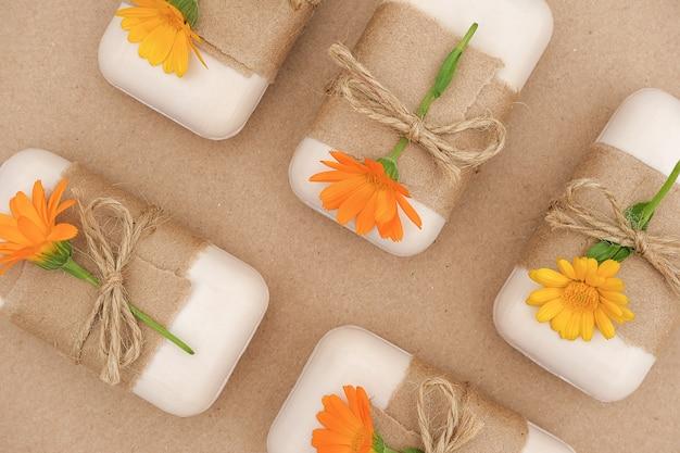 クラフト紙、スカージ、オレンジ色のキンセンカの花で飾られた手作りの天然石鹸セット。