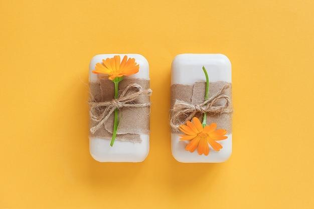 クラフト紙、スカージ、オレンジ色のキンセンカの花で飾られた手作りの天然石鹸セット