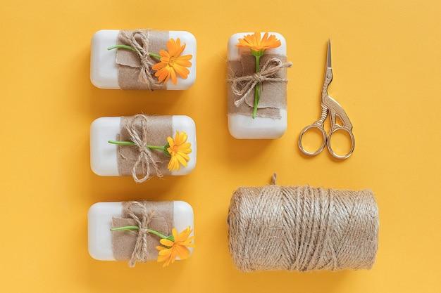 クラフト紙、オレンジ色のキンセンカの花、かせの糸とはさみで飾られた手作りの天然石鹸セット。