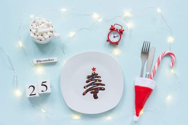 Сладкая шоколадная ёлка на тарелке, столовые приборы в новогодней шапке, чашка какао, будильник и дата