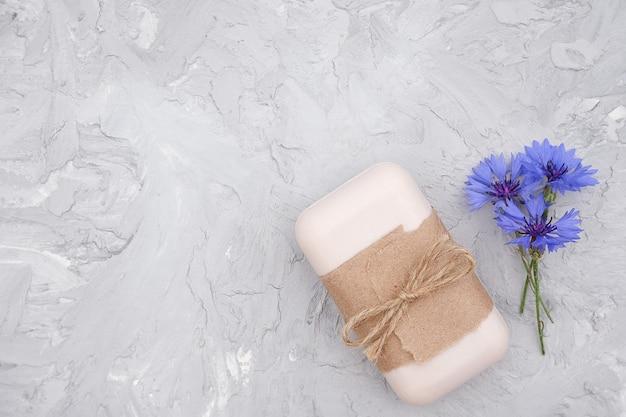 クラフト紙、惨劇、青い花で飾られた手作りの天然石鹸