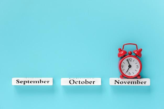 Деревянный календарь осенних месяцев и красный будильник на ноябрь