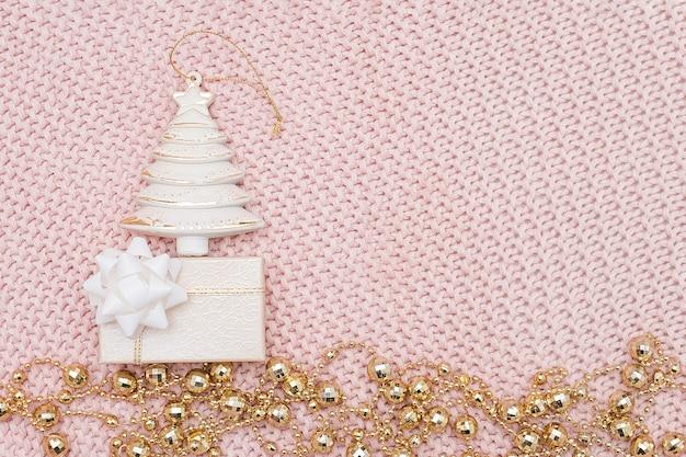 装飾的なベージュのクリスマスツリー、ギフトボックス、ピンクのニットの背景に金の花輪。新年やクリスマスのコンセプト。