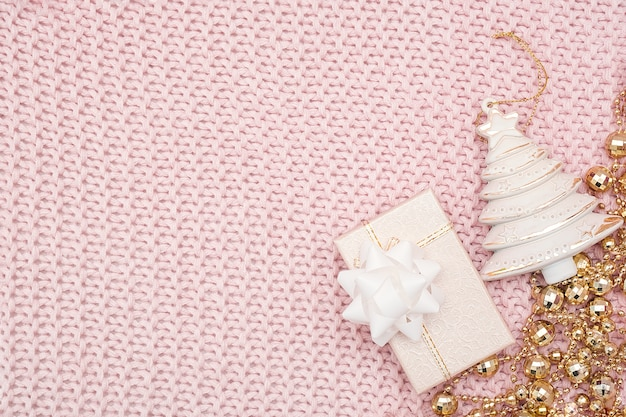 装飾的なベージュのクリスマスツリー、ギフトボックス、ピンクのニットの背景に金の花輪。新年やクリスマス。