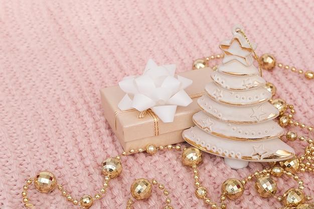 装飾クリスマスツリー、ギフトボックス、ピンクのニットの背景に金の花輪。新年やクリスマス。