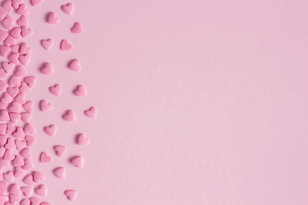 Розовые кондитерские сердца расположены на левой стороне на розовом фоне, открытка