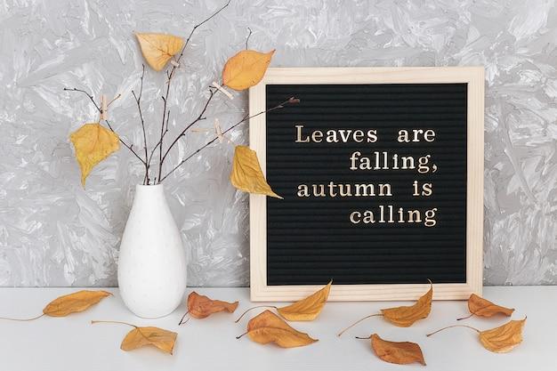 葉が落ちている、秋が呼んでいる、ブラックフレームボード上の動機付けの引用