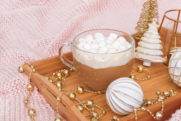 ココア、マシュマロ、暖かいニットピンクの格子縞のクリスマスの装飾のカップと木製のトレイ。