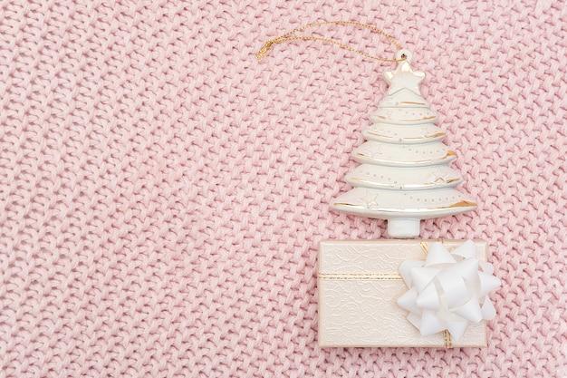 ピンクのニットの背景に装飾的なベージュのクリスマスツリーとギフトボックス。