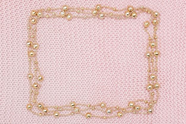ニットピンクの背景に金色のビーズの花輪から長方形のフレーム。