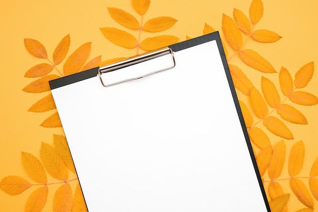 黄色の背景に白い空白の紙と秋のクリップボードを残します。